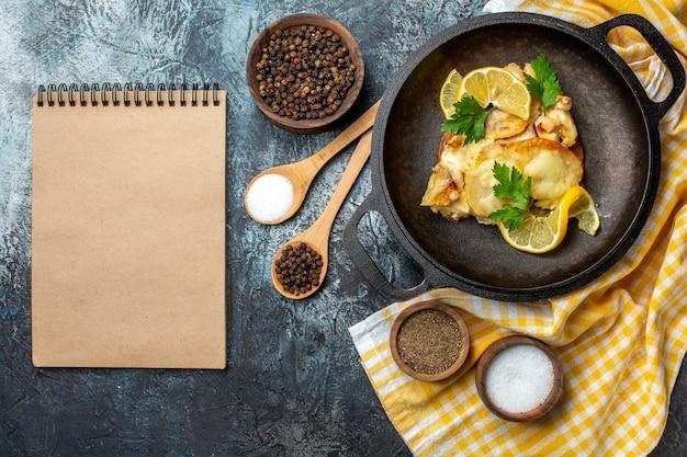 Pesce fritto vista dall'alto in padella con limone e prezzemolo su tovaglia a scacchi bianca gialla