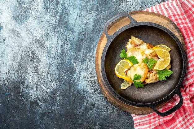 Vista dall'alto pesce fritto in padella su tavola di legno tovaglia a quadretti rossa e bianca su sfondo grigio