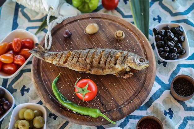 Top view fried fish with tomato chili pepper mushrooms on a tray with olives and spices on the table