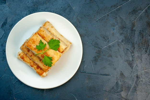 Vista dall'alto di involtini di lavash fritti su un piatto servito con verde sul lato destro su sfondo scuro