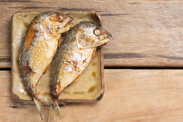 Top view of fried mackerel on wooden table.