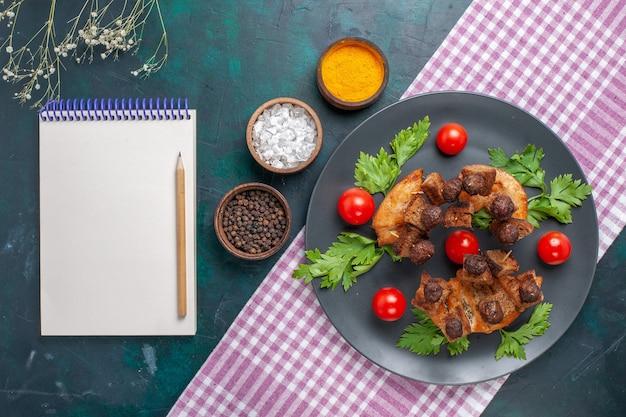 暗い表面の肉料理の食事野菜の稚魚のプレートの内側に緑のメモ帳とチェリートマトを添えた上面図揚げ肉スライス