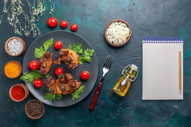 紺色の机の上のオリーブオイルと調味料で揚げた肉のスライスの上面図野菜料理肉健康食事
