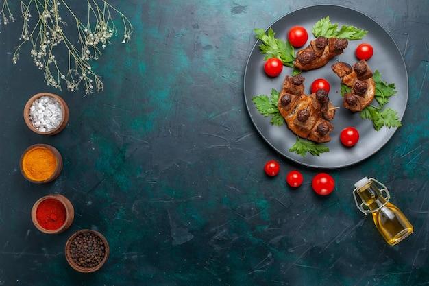 Вид сверху жареные кусочки мяса с оливковым маслом и приправами на темно-синем столе, овощная еда, мясо, здоровая еда