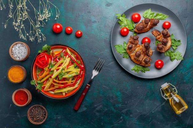 진한 파란색 책상 야채 음식 육류 건강 식사에 올리브 오일 샐러드와 조미료와 함께 상위 뷰 튀긴 고기 조각