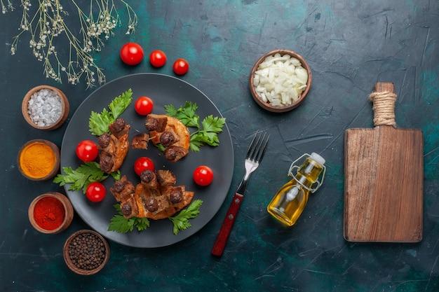 Vista dall'alto fette di carne fritte con olio d'oliva e condimenti sul pasto salutare di carne di cibo vegetale scrivania blu scuro