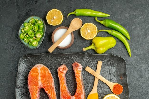 暗い机の上にピーマンとレモンと一緒に揚げた肉のスライスの上面図