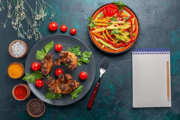 Vista dall'alto fette di carne fritta con blocco note di insalata di verdure a fette e condimenti sul pasto salutare di carne di cibo vegetale da scrivania blu scuro