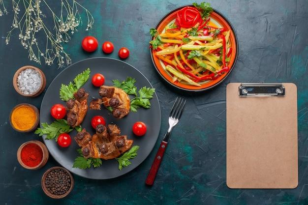 Vista dall'alto fette di carne fritta con insalata di verdure a fette e condimenti sul pasto salutare di carne di cibo vegetale da scrivania blu scuro