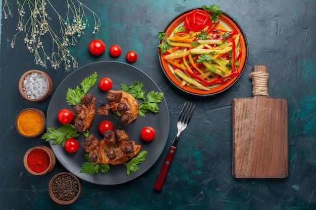 Vista dall'alto fette di carne fritta con insalata di verdure a fette e condimenti sul pasto salutare di carne di cibo di verdure da scrivania blu scuro