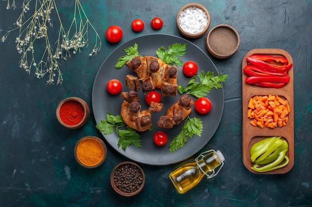 Вид сверху жареные кусочки мяса с овощами и приправами на темно-синем столе овощи еда еда мясо ужин здоровье