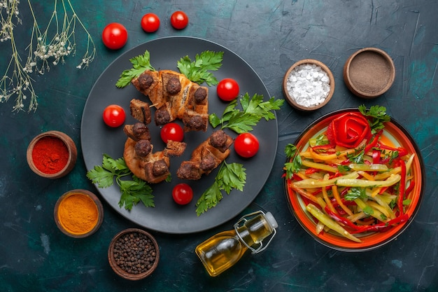Вид сверху жареные кусочки мяса с овощами и приправами на темно-синей поверхности овощная еда еда мясной ужин здоровье