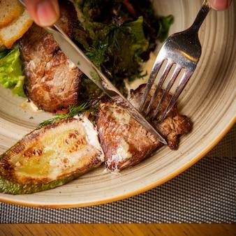 Вид сверху жареное мясо с жареными цуккини и вилкой и ножом и зеленью в круглой тарелке