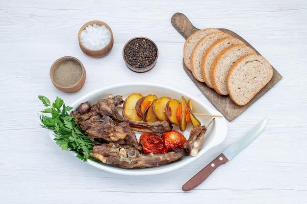 Vista dall'alto di carne fritta con verdure e prugne al forno all'interno del piatto con pagnotte di pane sulla cena leggera, pasto di carne