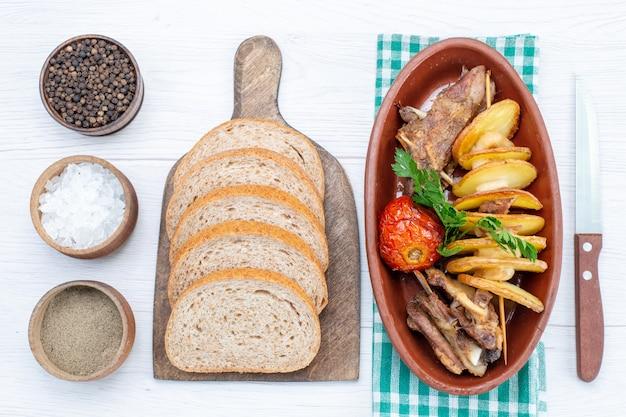 Vista dall'alto di carne fritta con verdure e prugne al forno all'interno della piastra con pagnotte di pane sale sulla scrivania leggera, pasto a base di carne cena vegetale