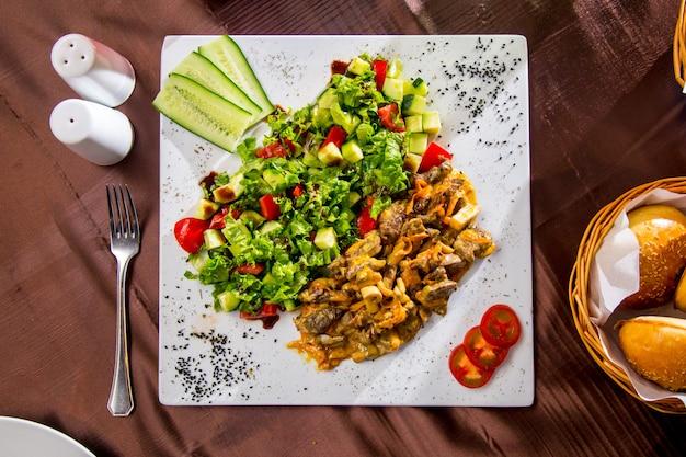 Vista superiore carne fritta con funghi in salsa con insalata di verdure e fette di pomodoro e cetriolo