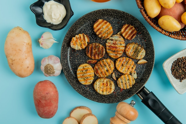 Top view of fried potato slices in frying pan with uncooked ones in basket mayonnaise garlic salt black pepper on blue