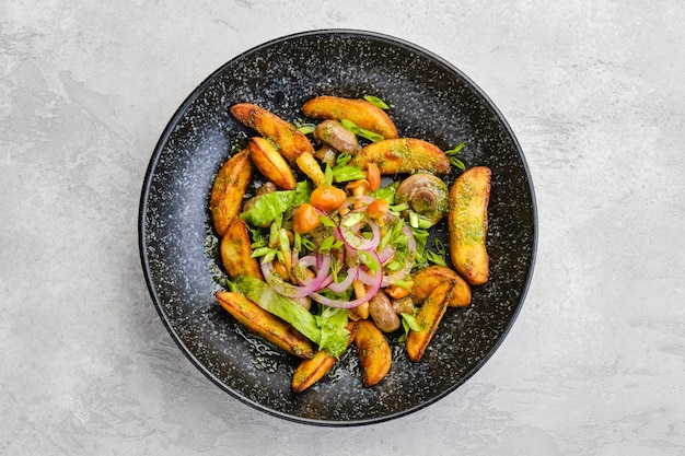 Top view of fried potato wedges with champignons dressed with red and white onion