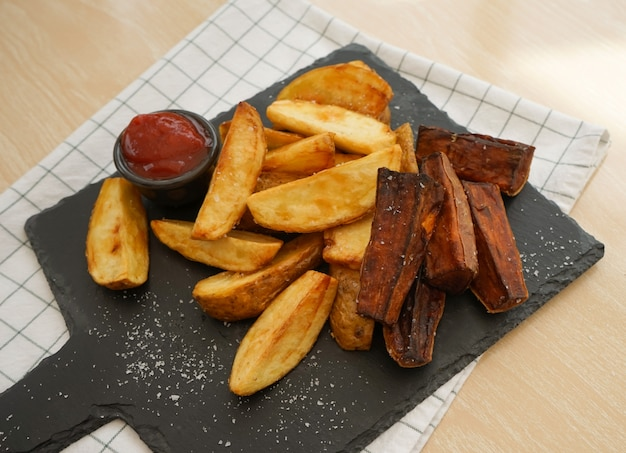 Top view of fried potatoes and baked sweet potato on black slate plate severed with tomato sauce