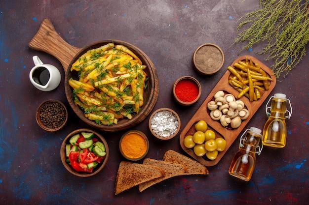 Vista dall'alto patate fritte gustose patatine fritte con verdure e condimenti diversi su superficie scura