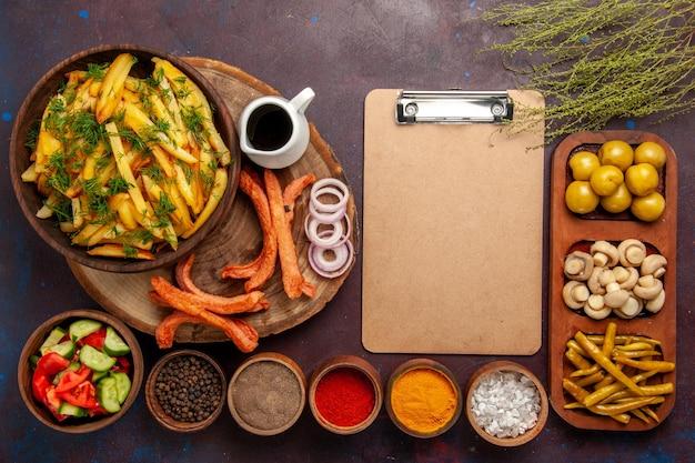 Вид сверху жареный картофель с разными приправами и разными овощами на темной поверхности