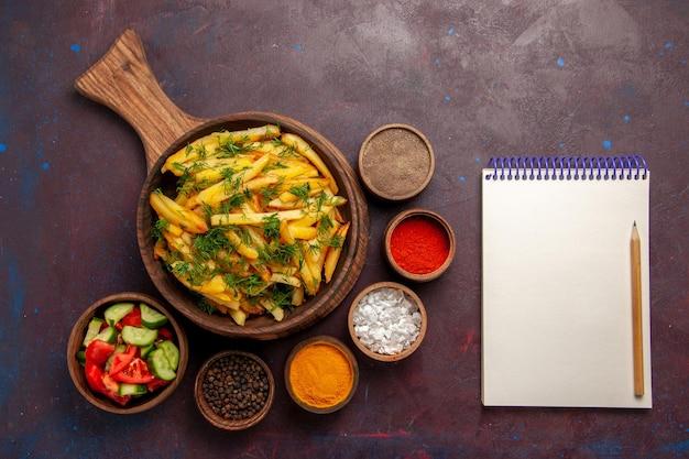Patate fritte vista dall'alto con verdure e condimenti diversi sulla scrivania scura