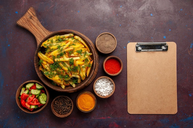 Patate fritte vista dall'alto con verdure e condimenti diversi su superficie scura