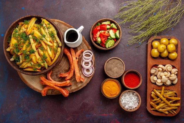 Вид сверху жареный картофель с приправами и разными овощами на темном столе