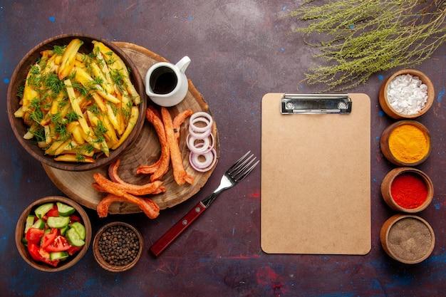 暗い表面に調味料とさまざまな野菜を添えたフライドポテトの上面図
