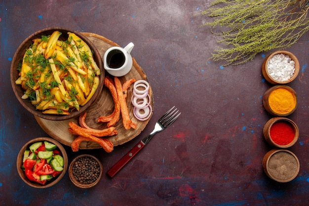 Вид сверху жареный картофель с приправами и разными овощами на темной поверхности