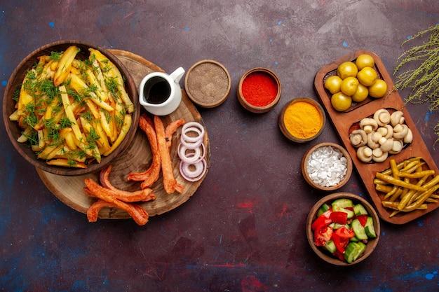 暗い机の上に調味料とさまざまな野菜を添えたトップビューフライドポテト