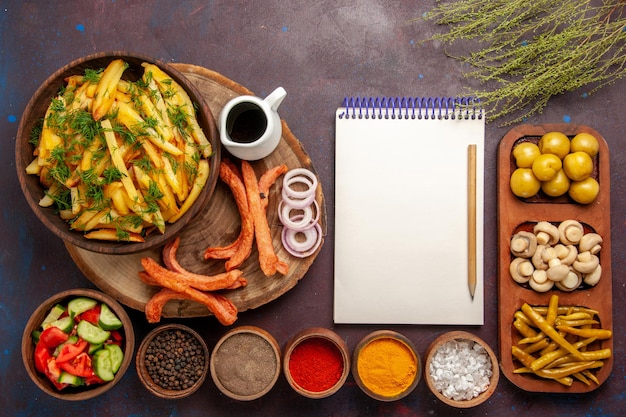 Top view fried potatoes with seasonings bread and different vegetables on dark desk
