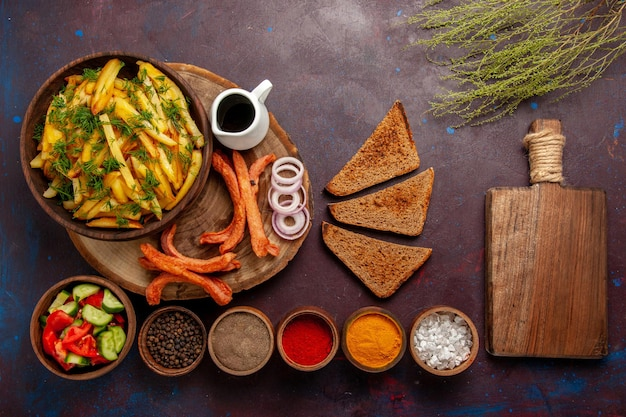 Top view fried potatoes with seasonings bread and different vegetables on dark surface