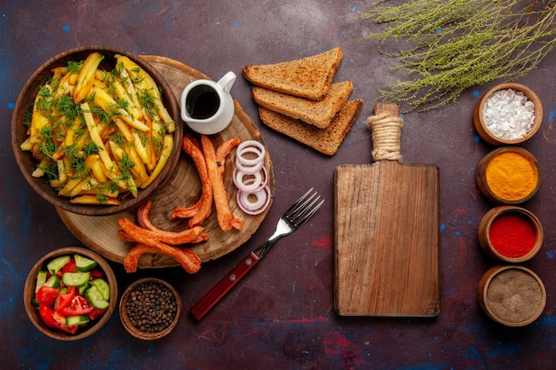 Top view fried potatoes with seasonings bread loafs and different vegetables on dark surface