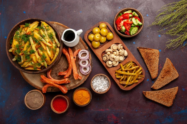 Vista dall'alto patate fritte con condimenti pagnotte di pane e verdure diverse sulla superficie scura