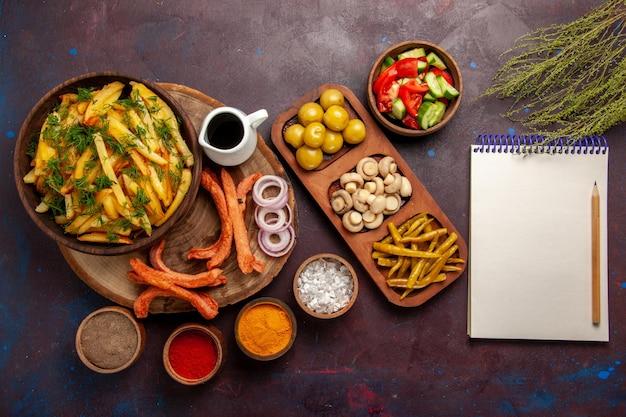 Patate fritte vista dall'alto con condimenti e verdure diverse su superficie scura