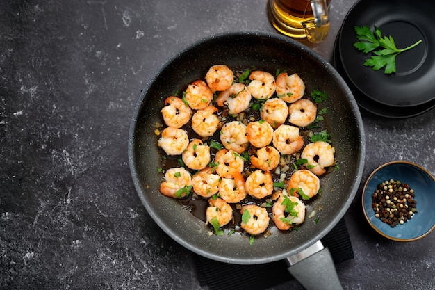 Top view of fried prawns in a pan on black table