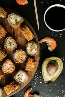 Vista dall'alto involtini fritti con bastoncini di granchio su un supporto con semi di sesamo salsa di soia avocado e gamberi bolliti