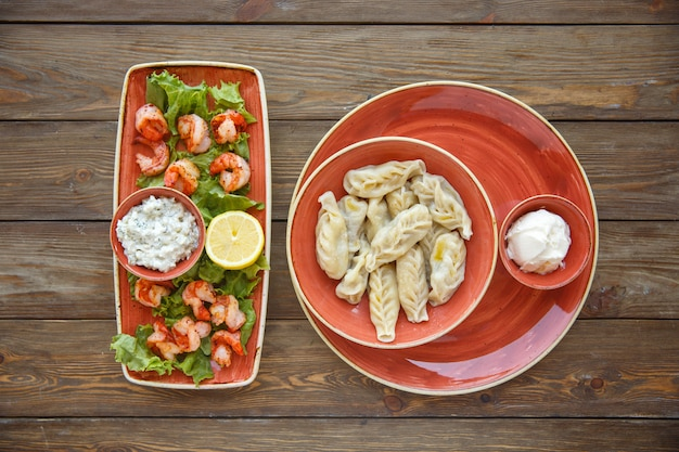 Top view of fried shrimps with lemon and sauce and gurza with yoghurt