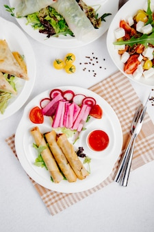 Top view of fried spring rolls with vegetables and sauce