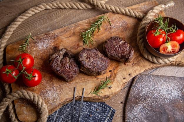 Вид сверху жареное вкусное мясо со свежими красными помидорами и зеленью на деревянном столе еда ужин мясо фото