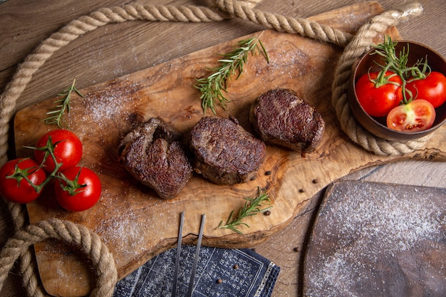 Top view fried tasty meat with fresh red tomatoes and greens on the wooden desk meal food dinner meat photo