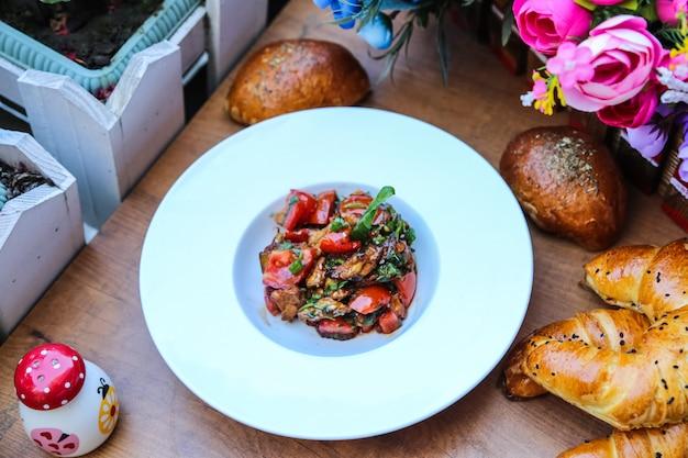 テーブルの上のパンと皿の上の野菜炒めのトップビュー