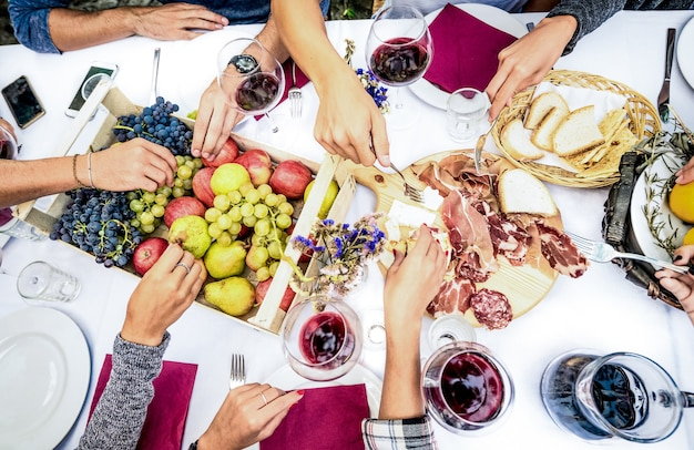 Top view of friend hands eating food and wine at barbecue garden party