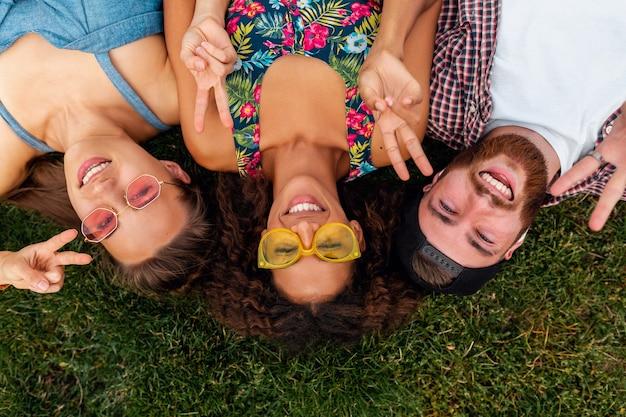 公園の芝生の上に横たわって、男性と女性が一緒に楽しんでいる友人のカラフルでスタイリッシュな幸せな若い会社の上からの上面図