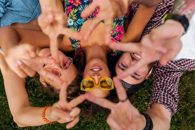 공원에서 잔디에 누워 친구의 화려한 세련 된 행복 젊은 회사 위에서 상위 뷰, 남자와 여자는 함께 재미