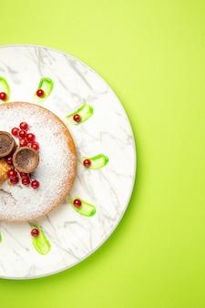 遠くからの上面図ケーキプレートにワッフル赤スグリ粉砂糖を添えたケーキ