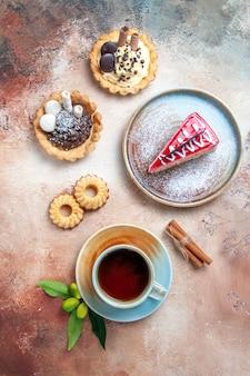 遠くからの上面図一杯のお茶一杯のお茶カップケーキクッキーケーキプレート上の