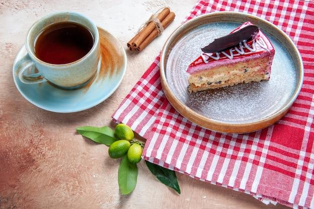 遠くからの上面図一杯のお茶市松模様のテーブルクロスのケーキの横にある一杯のお茶