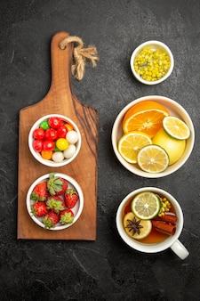 Вид сверху на чашку чая с разноцветными конфетами и клубникой на деревянной разделочной доске рядом с мисками с травами и нарезанными лимонами и чашкой чая, вид сверху издалека